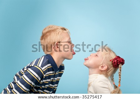 Teenage boy and girl stick out tongues to each other
