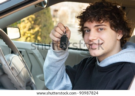 Teenage boy and new driver behind wheel of his car holding keys - stock photo