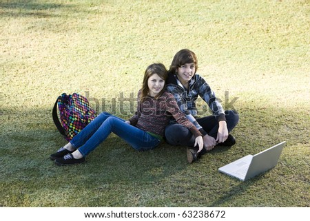 Teenage boy and preteen girl sitting on grass with laptop, online in park