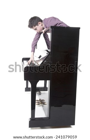 teenage boy and upright black piano in studio with white background - stock photo