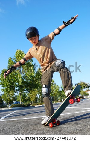Teenage boy balancing on a skateboard in a parking lot on a sunny day with blue sky and trees in the background. - stock photo