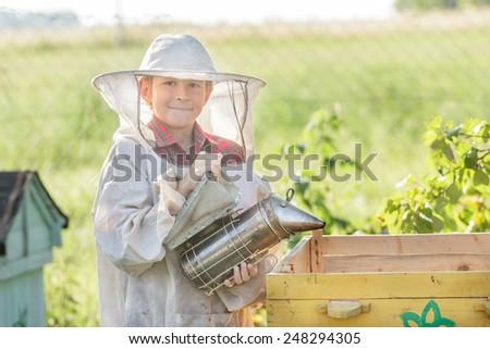 Teenage boy beekeeper is wearing protective clothing - stock photo