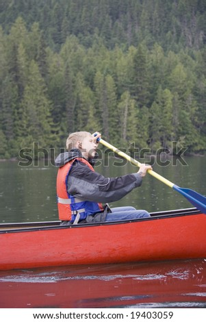 Teenage boy canoeing in Canada - stock photo