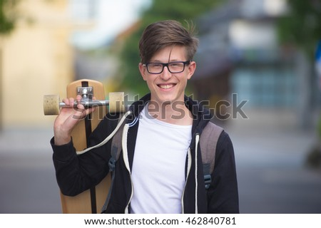 Teenage boy carrying a long-board and wearing a school backpack.