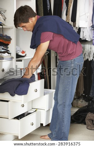Teenage Boy Choosing Clothes From Wardrobe In Bedroom