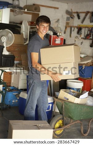 Teenage Boy Clearing Garage For Yard Sale - stock photo