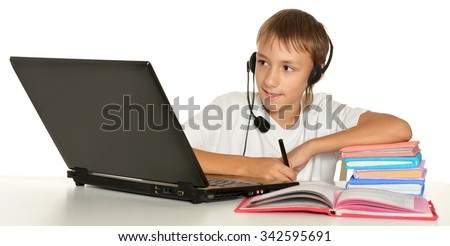Teenage boy doing homework with a laptop - stock photo