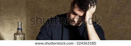 Teenage boy drinking vodka alone at home - stock photo