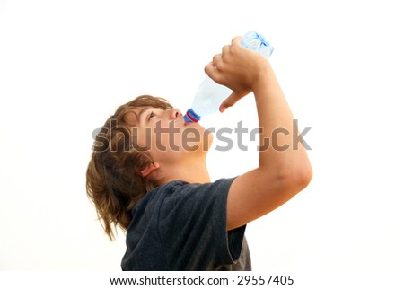Teenage boy drinking water from a plastic bottle isolated on white background. - stock photo