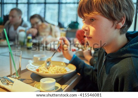 Teenage boy eats sitting at table in cafe.