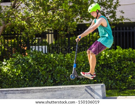 teenage boy has fun riding his push scooter at the skate park - stock photo