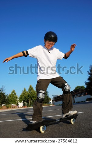 Teenage boy having fun skateboarding on a parking lot on a sunny day.