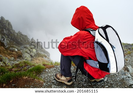 Teenage boy hiker in rain coat resting after hiking on mountain trail - stock photo
