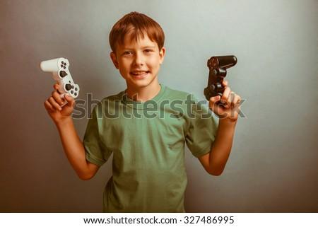 Teenage boy holding a game joystick on a blue background studio photo retro - stock photo