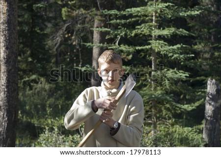 teenage boy holding an axe - stock photo