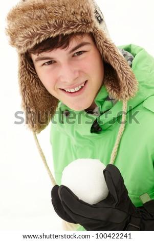 Teenage Boy Holding Snowball Wearing Fur Hat - stock photo