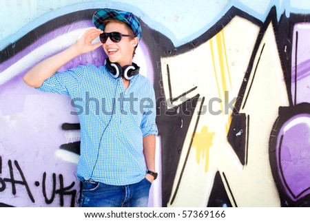 Teenage boy in front of graffiti - stock photo
