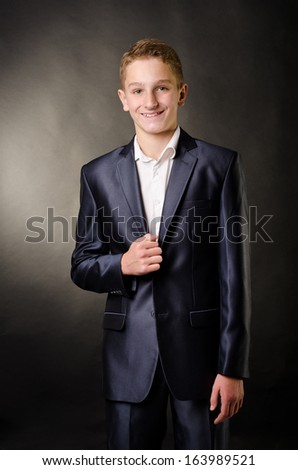 teenage boy in suit on a black background - stock photo