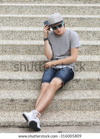 Teenage boy  in urban background.Using smart phone - stock photo