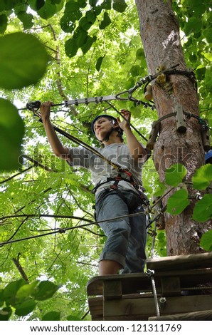Teenage boy is standing on the platform high up on the tree. He is photographed from below at the rope parkour outdoors. - stock photo