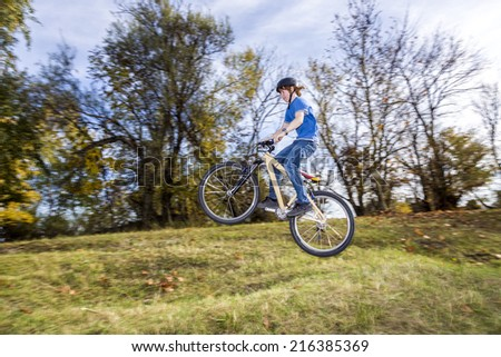 teenage boy jumps over a ramp with his dirt bike - stock photo