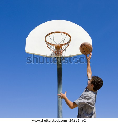 Teenage boy jumps to dunk a basketball - stock photo