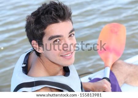 Teenage boy kayaking - stock photo