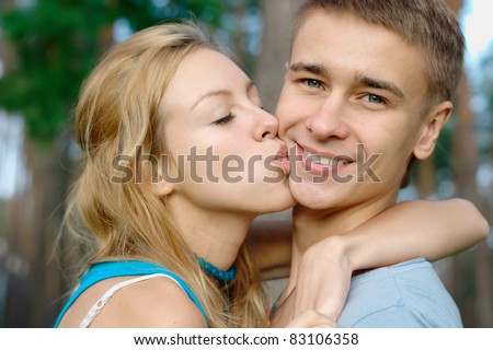 Teenage boy kissed by his girlfriend - stock photo