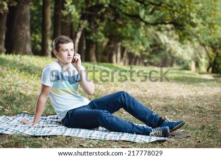 Teenage Boy Laying In Park Using Mobile Phone