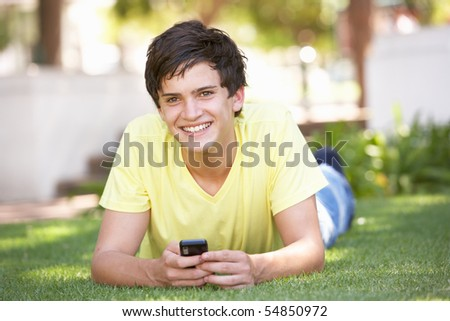 Teenage Boy Laying In Park Using Mobile Phone - stock photo