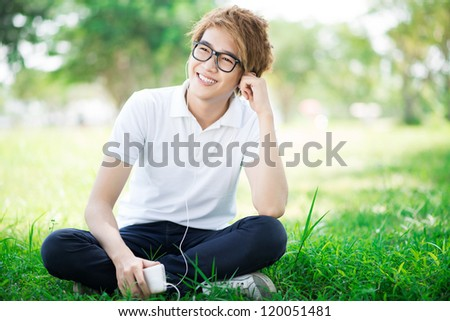 Teenage boy listening to mp3 outdoors - stock photo