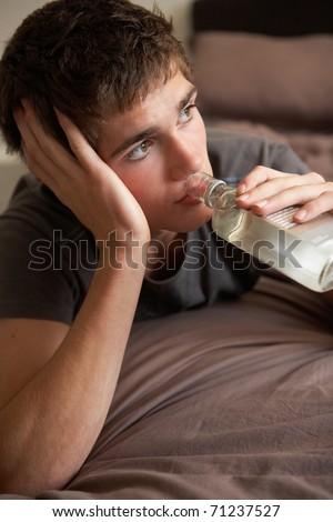 Teenage Boy Lying  In Bedroom Drinking - stock photo