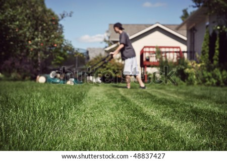 Teenage boy mowing lawn (extremely shallow depth of field, focus in foreground) - stock photo