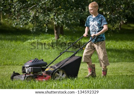 Teenage Boy Mowing Lawn Using Lawn Mower - stock photo