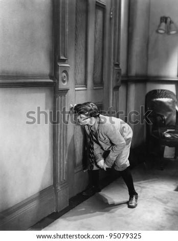 Teenage boy peeping through keyhole - stock photo