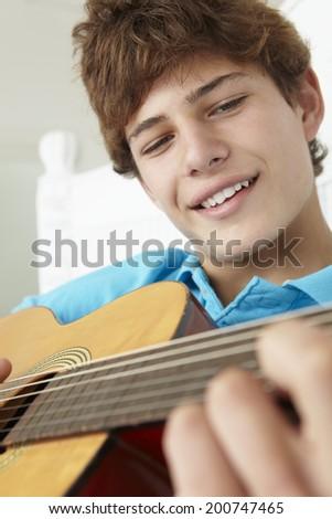 Teenage boy playing acoustic guitar - stock photo
