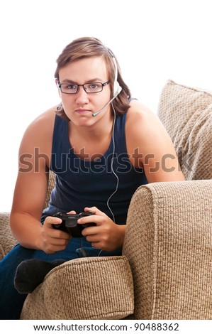 Teenage boy playing an intense game on his online video system while talking to other players worldwide. White background - stock photo