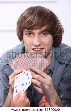 Teenage boy playing cards - stock photo