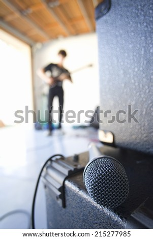Teenage boy (16-18) playing electric guitar in garage, focus on microphone in foreground - stock photo
