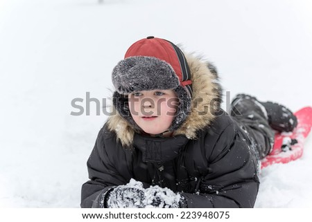 Teenage boy playing in the snow in winter - stock photo