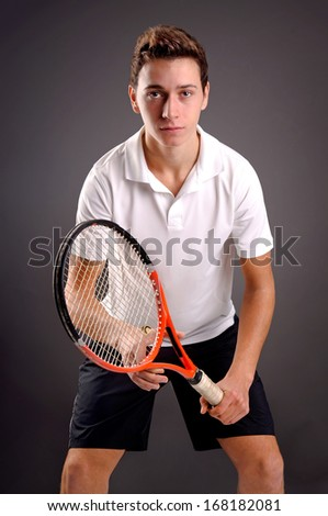 teenage boy playing tennis isolated in dark background - stock photo