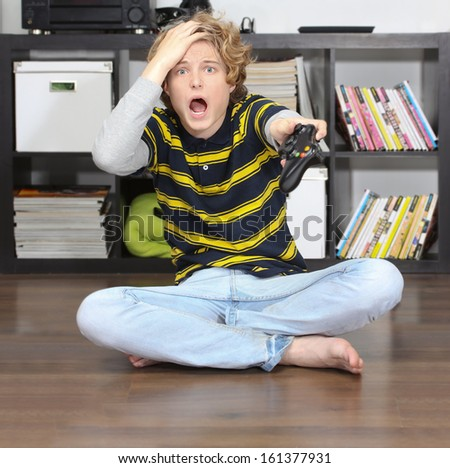 Teenage boy playing video game with joystick - stock photo