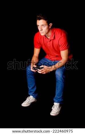 teenage boy playing videogames isolated on dark background - stock photo
