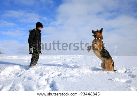 Teenage boy playing with dog in winter, sunny day on a meadow covered with snow. - stock photo