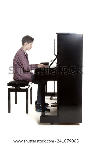 teenage boy plays the piano in studio with white background - stock photo