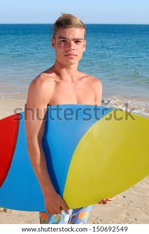teenage boy posing with surf board in the beach - stock photo