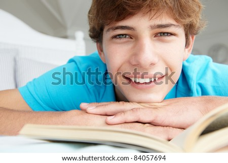 Teenage boy reading a book - stock photo