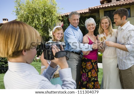 Teenage boy recording happy moments of family celebrating together at garden - stock photo