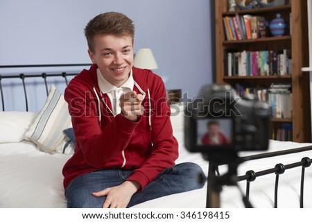 Teenage Boy Recording Video Of Himself In Bedroom - stock photo