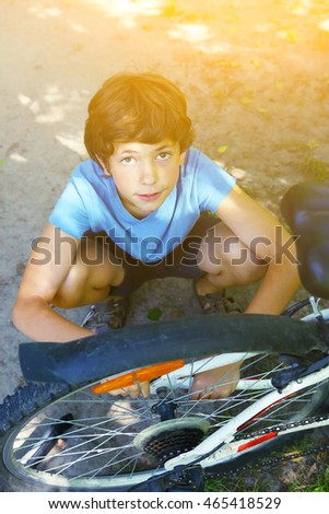 teenage boy repair bicycle wheel close up summer photo on the sunny garden country background